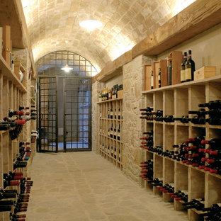 Inspiration för en mycket stor lantlig vinkällare, med vinhyllor