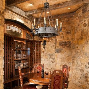 Cette photo montre une grand cave à vin chic avec des casiers, un sol en carreau de terre cuite et un sol beige.