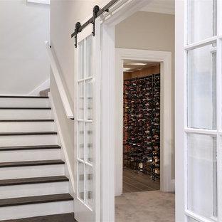 Foto de bodega clásica con suelo de madera clara, botelleros y suelo beige