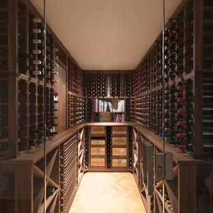 Idéer för att renovera en stor vintage vinkällare, med ljust trägolv och vinhyllor