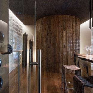 Imagen de bodega contemporánea con suelo de madera oscura y botelleros