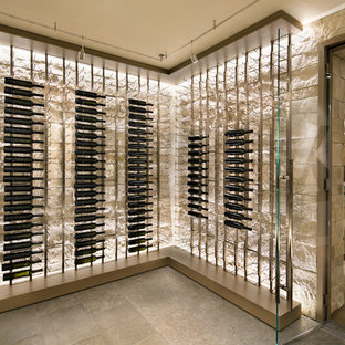 Modern inredning av en stor vinkällare, med skiffergolv, vinhyllor och grått golv