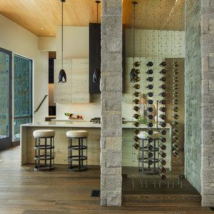 Inredning av en rustik mellanstor vinkällare, med mellanmörkt trägolv, vinhyllor och brunt golv