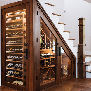Bild på en liten vintage vinkällare, med mörkt trägolv, vinhyllor och brunt golv