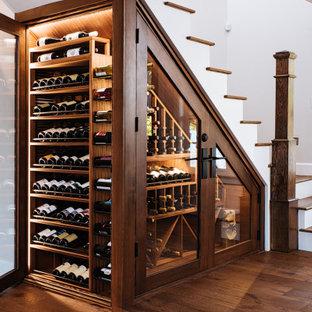 Cette image montre une petit cave à vin traditionnelle avec un sol en bois foncé, des casiers et un sol marron.