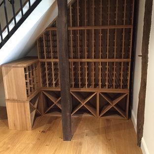 Bild på en liten funkis vinkällare, med vinhyllor, ljust trägolv och brunt golv