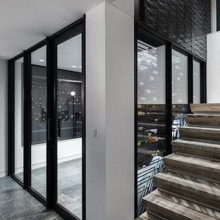 Diseño de bodega minimalista, grande, con suelo de piedra caliza, vitrinas expositoras y suelo negro