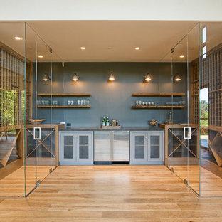 Idee per una cantina contemporanea con pavimento in legno massello medio e rastrelliere portabottiglie