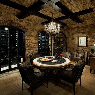 Cette photo montre une très grand cave à vin chic avec des casiers, un sol en travertin et un sol marron.