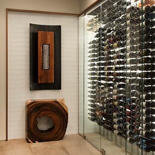 Bild på en stor funkis vinkällare, med kalkstensgolv, vindisplay och beiget golv