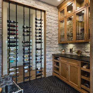 Imagen de bodega clásica renovada, grande, con suelo de baldosas de porcelana, botelleros y suelo negro