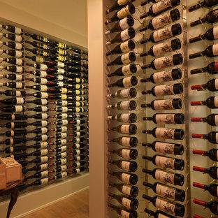 Bild på en mellanstor funkis vinkällare, med vindisplay, ljust trägolv och brunt golv
