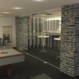 Cette photo montre une cave à vin moderne de taille moyenne avec béton au sol et un présentoir.