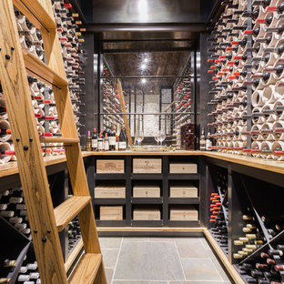 Example of a mid-sized urban gray floor and slate floor wine cellar design in Other with diamond bins
