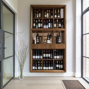 Modern inredning av en mellanstor vinkällare, med mellanmörkt trägolv, vindisplay och beiget golv