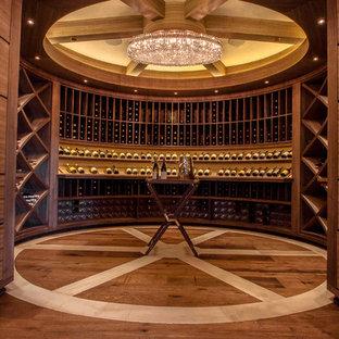Diseño de bodega clásica con suelo de madera en tonos medios y botelleros