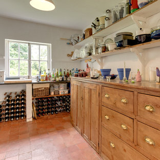 This is an example of a farmhouse wine cellar in Other with brick flooring and storage racks.