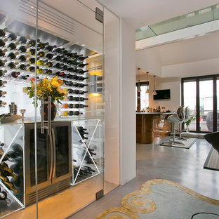 Contemporary wine cellar in London with concrete flooring.