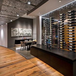 Foto på en mycket stor funkis vinkällare, med mellanmörkt trägolv och vinhyllor