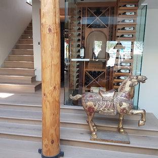Ejemplo de bodega de estilo americano, pequeña, con suelo de madera clara, vitrinas expositoras y suelo beige