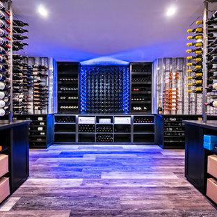 Cette image montre une grand cave à vin minimaliste avec un sol en carrelage de porcelaine, un présentoir et un sol gris.