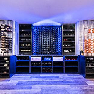 Modern inredning av en stor vinkällare, med klinkergolv i porslin, vindisplay och grått golv