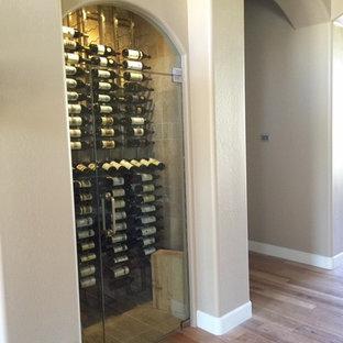 Inredning av en modern mellanstor vinkällare, med travertin golv och vinhyllor