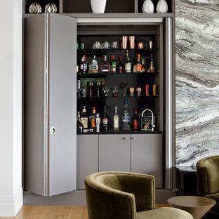 Imagen de bodega moderna, extra grande, con suelo de madera clara, vitrinas expositoras y suelo marrón
