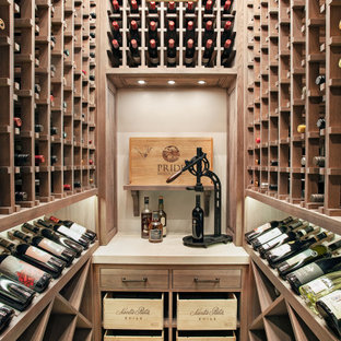Example of a small transitional travertine floor and beige floor wine cellar design in Houston with display racks
