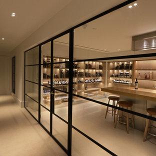 Cette image montre une grand cave à vin design avec un sol en calcaire, un présentoir et un sol blanc.