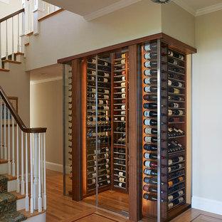 Diseño de bodega clásica renovada con suelo de madera en tonos medios y botelleros