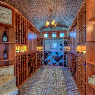 Aménagement d'une cave à vin classique avec un sol en brique, un présentoir et un sol rouge.
