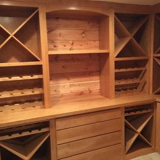 Réalisation d'une cave à vin tradition de taille moyenne avec un sol en carrelage de porcelaine et des casiers losange.