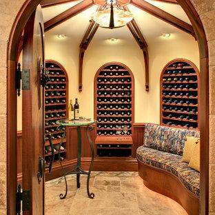 Exempel på en stor rustik vinkällare, med kalkstensgolv, vinhyllor och beiget golv