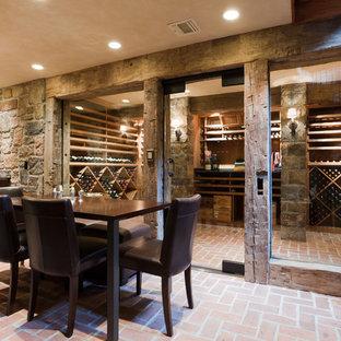 Aménagement d'une très grand cave à vin montagne avec des casiers losange, un sol en brique et un sol rouge.