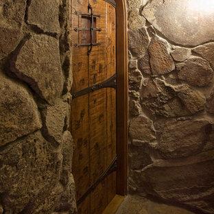 Ejemplo de bodega rural, de tamaño medio, con suelo de piedra caliza, botelleros y suelo marrón