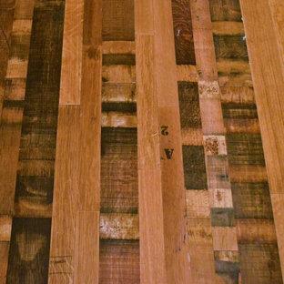 Ejemplo de bodega tradicional, pequeña, con suelo de madera en tonos medios y vitrinas expositoras