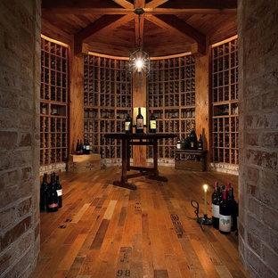 Inspiration för stora medelhavsstil vinkällare, med mörkt trägolv och vinhyllor