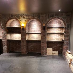 Ispirazione per una grande cantina rustica con pavimento in gres porcellanato, portabottiglie a vista e pavimento grigio