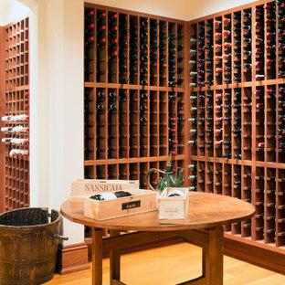 Foto de bodega clásica, grande, con suelo de madera clara, botelleros y suelo naranja