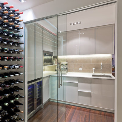 Example of a small trendy dark wood floor and red floor wine cellar design in Auckland with storage racks