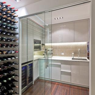 Foto på en liten funkis vinkällare, med mörkt trägolv, vinhyllor och rött golv