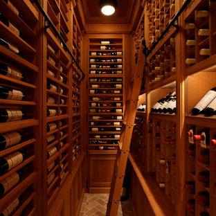 Cette image montre une grand cave à vin traditionnelle avec des casiers et un sol en brique.