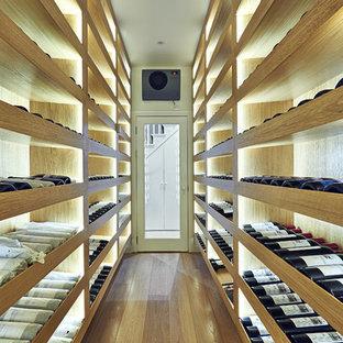 Medium sized contemporary wine cellar in London with light hardwood flooring and storage racks.
