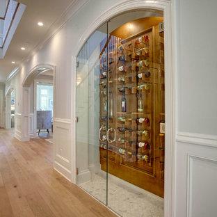 Cette photo montre une petit cave à vin chic avec un présentoir, un sol blanc et un sol en marbre.