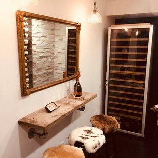 Cette image montre une petit cave à vin chalet avec un sol en contreplaqué, des casiers et un sol noir.