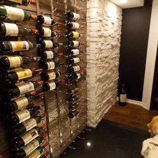 Foto på en liten rustik vinkällare, med plywoodgolv, vinhyllor och svart golv