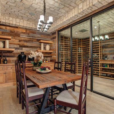 Elegant light wood floor and beige floor wine cellar photo in Orange County with storage racks