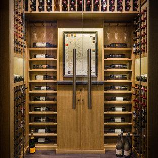 Cette photo montre une petit cave à vin tendance avec un sol en bois foncé et un présentoir.