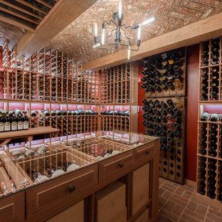 Bild på en stor vintage vinkällare, med tegelgolv, vinhyllor och rött golv